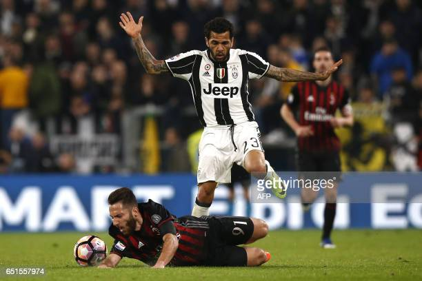 Juventus' defender Daniel Alves from Brazil fights for the ball with AC Milan's midfielder Andrea Bertolacci during the Italian Serie A football...
