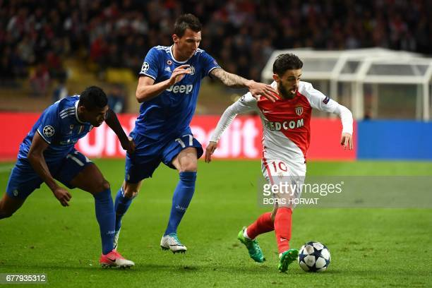 Juventus' defender from Brazil Alex Sandro and Juventus' forward from Croatia Mario Mandzukic fights for the ball against Monaco's Portuguese...