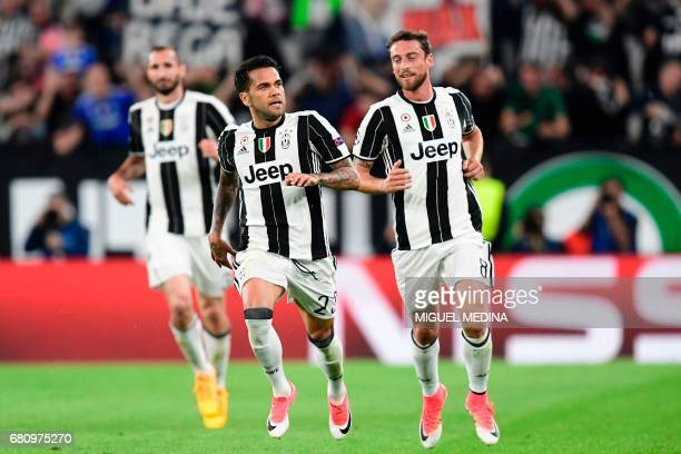Juventus Defender from Brazil Dani Alves celebrates with teammate Juventus' midfielder from Italy Claudio Marchisio after scoring during the UEFA...