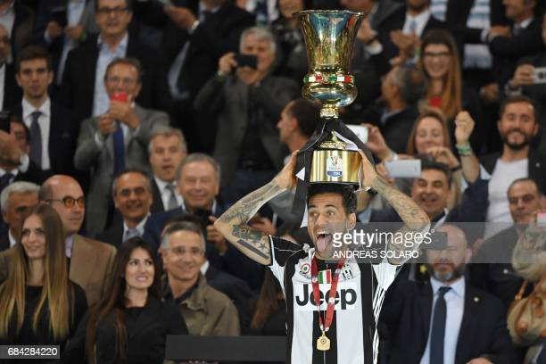 TOPSHOT Juventus Defender from Brazil Dani Alves holds the trophy after winning the Italian Tim Cup final on May 17 2017 at the Olympic stadium in...