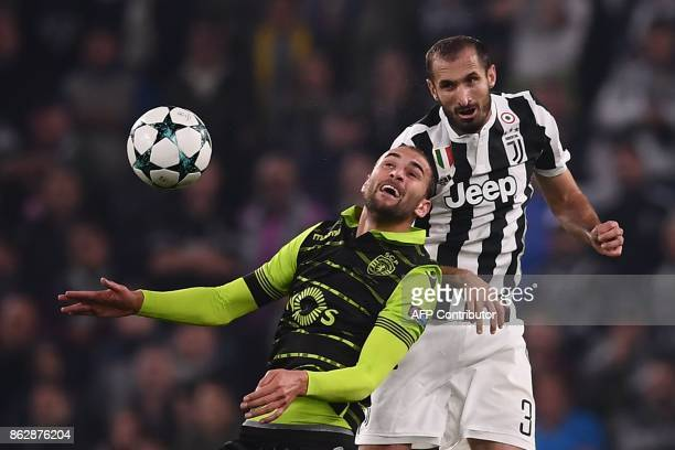 Juventus' defender from Italy Giorgio Chiellini and Sporting's Dutch forward Bas Dost jump for the ball during the UEFA Champions League Group D...