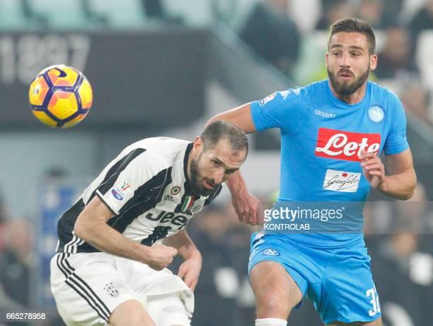 Juventus' defender from Italy Giorgio Chiellini heads the ball as fighting with Napoli's Italian forward Leonardo Pavoletti during the first leg...