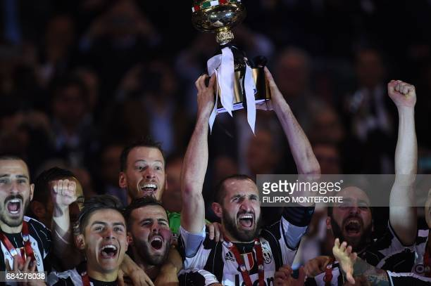 TOPSHOT Juventus' defender from Italy Giorgio Chiellini holds the trophy with teammates Juventus' defender from Italy Leonardo Bonucci Juventus'...