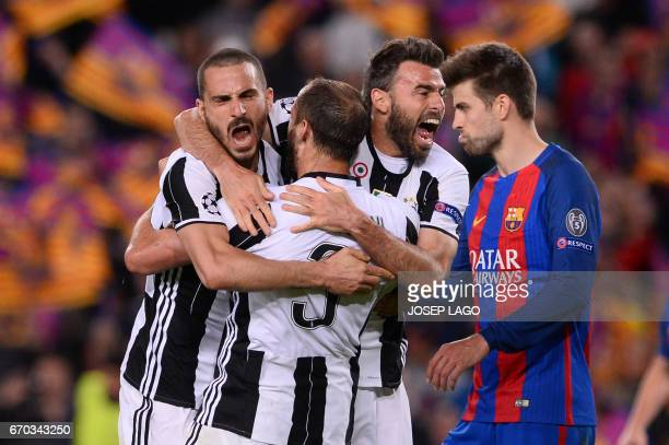TOPSHOT Juventus' defender Giorgio Chiellini celebrates their qualification with Juventus' defender Andrea Barzagli and a teammate at the end of the...