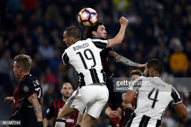 Juventus' defender Leonardo Bonucci and AC Milan's defender Alessio Romagnoli jump for the ball during the Italian Serie A football match Juventus Vs...