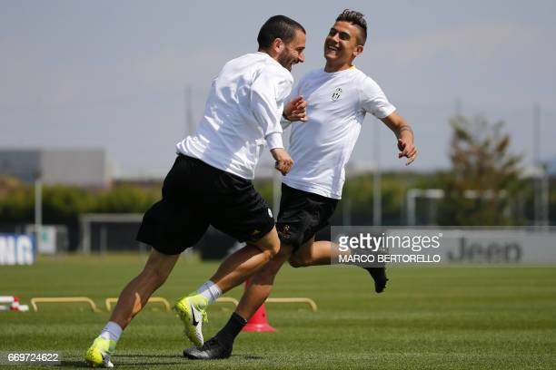 Juventus' defender Leonardo Bonucci and Juventus' forward Paulo Dybala from Argentina take part in a training session on the eve of the UEFA...