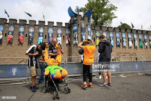 Juventus Fans with a cuddly teddy bear toy stand outside Cardiff Castle which bears a giant dragon and Champions League trophy ahead of the UEFA...