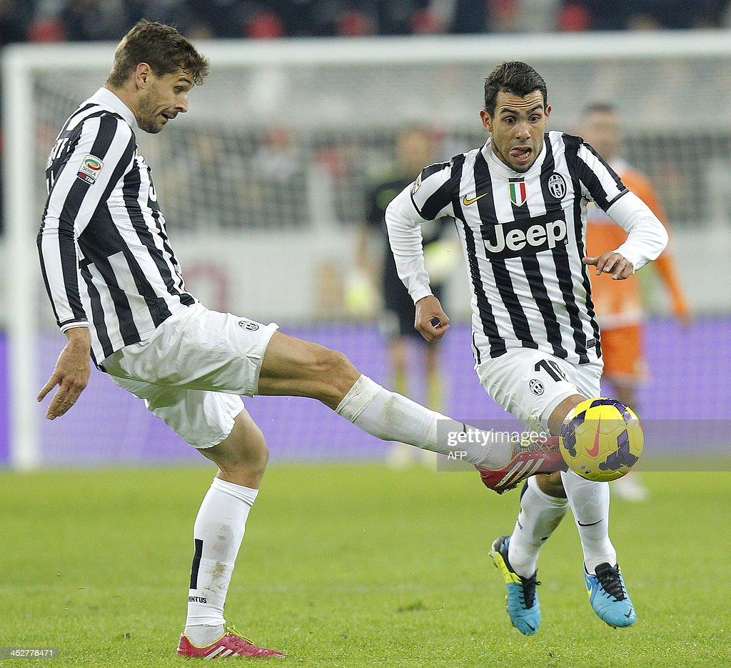 Juventus' forward Fernando Llorente passes the ball to teammate forward Carlos Tevez during the Italian Serie A football match Juventus Vs Udinese on December 1, 2013 at Juventus Stadium in Turin.
