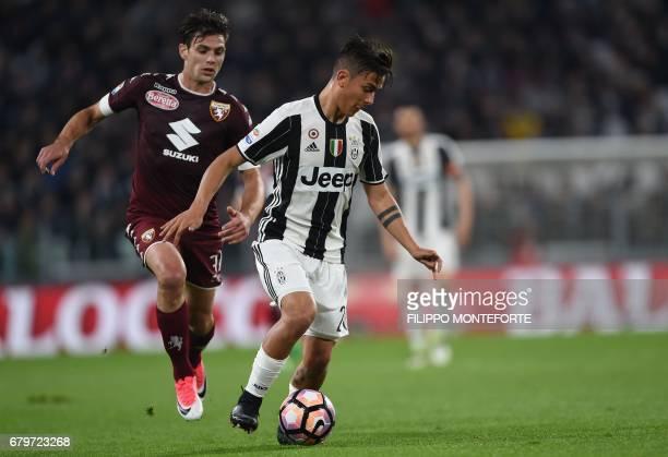 Juventus forward frm Argentina Paulo Dybala vies with Torino's forward form Argentina Lucas Boyé during the Italian Serie A football match Juventus...