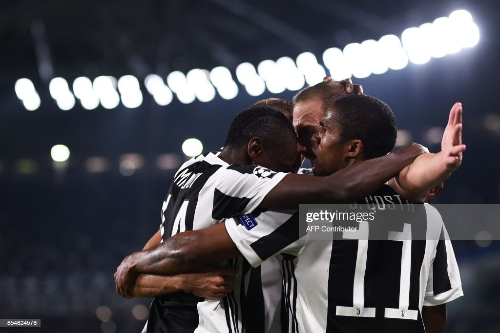Juventus' forward from Argentina Gonzalo Higuain (R) celebrates with teammates Juventus' midfielder from France Blaise Matuidi and Juventus' forward from Brazil Douglas Costa (R) after scoring during the UEFA Champion's League Group D football match Juventus vs Olympiacos on September 27, 2017 at the Juventus stadium in Turin. /