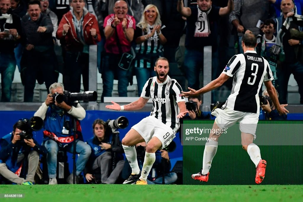 Juventus' forward from Argentina Gonzalo Higuain (L) celebrates with Juventus' defender from Italy Giorgio Chiellini after scoring during the UEFA Champion's League Group D football match Juventus vs Olympiacos on September 27, 2017 at the Juventus stadium in Turin. Juventus won 2-0. / AFP PHOTO / Miguel MEDINA