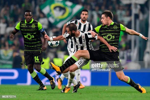 Juventus' forward from Argentina Gonzalo Higuain fights for the ball with Sporting's Uruguayan defender Sebastien Coates and Sporting's midfielder...