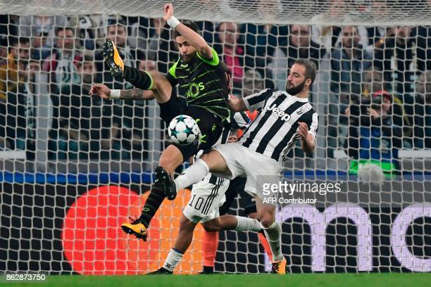 Juventus' forward from Argentina Gonzalo Higuain fights for the ball with Sporting's Uruguayan defender Sebastien Coates uring the UEFA Champions...