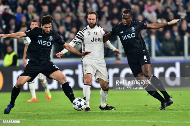 Juventus' forward from Argentina Gonzalo Higuain vies with Porto's French defender Willy Boly and Porto's Brazilian midfielder Otavio during the UEFA...