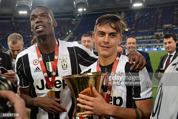 Juventus' forward from Argentina Paulo Dybala and Juventus' midfielder from France Paul Pogba celebrate with the trophy after winning the Italian Tim...