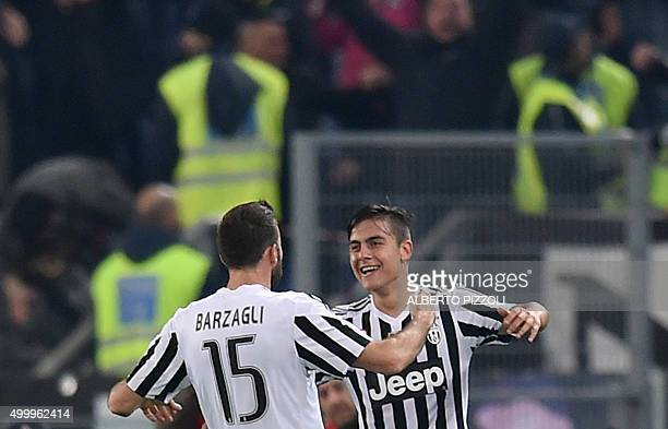 Juventus' forward from Argentina Paulo Dybala celebrates after scoring with Juventus' defender from Italy Andrea Barzagli during the Italian Serie A...
