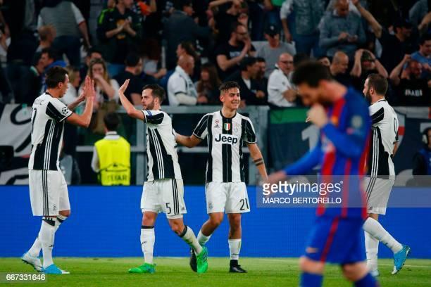 Juventus' forward from Argentina Paulo Dybala celebrates with teammates Juventus' forward from Croatia Mario Mandzukic Juventus midfielder Miralem...