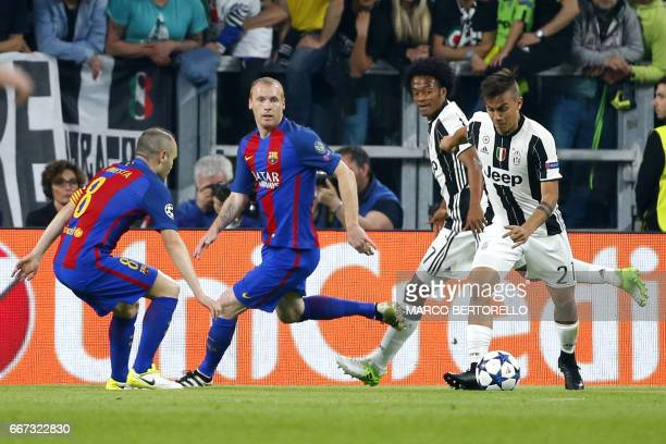 Juventus' forward from Argentina Paulo Dybala controls the ball next to Juventus' forward from Colombia Juan Cuadrado and Barcelona's midfielder...