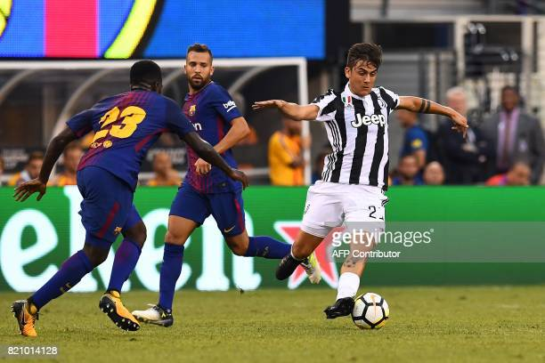 Juventus' forward from Argentina Paulo Dybala dodges past Barcelona's French defender Samuel Umtiti during the International Champions Cup match...