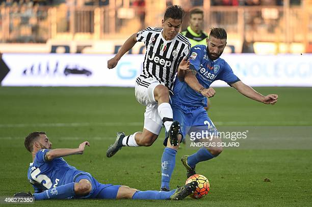 Juventus' forward from Argentina Paulo Dybala fights for the ball with Empoli's defender from Italy Lorenzo Tonelli and Empoli's defender from Italy...