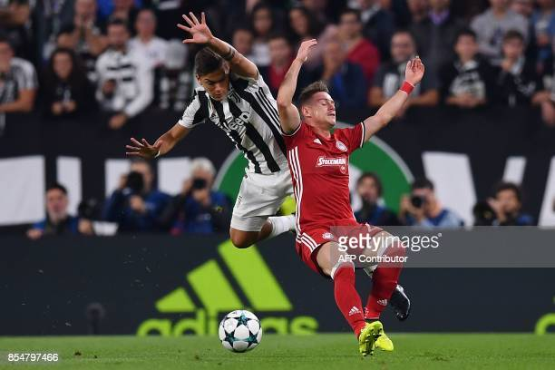 Juventus' forward from Argentina Paulo Dybala fights for the ball with Olympiacos' Nigerian Defender Emmanuel Emenike during the UEFA Champion's...