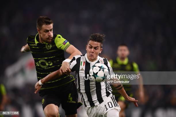 Juventus' forward from Argentina Paulo Dybala fights for the ball with Sporting's Uruguayan defender Sebastien Coates during the UEFA Champions...