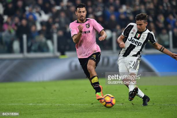 Juventus' forward from Argentina Paulo Dybala kicks and scores flanked by Palermo's defender from Slovenia Sinisa Andelkovic during the Italian Serie...