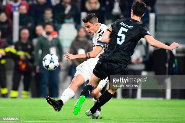 Juventus' forward from Argentina Paulo Dybala kicks in front of Porto's Spanish defender Ivan Marcano during the UEFA Champions League football match...