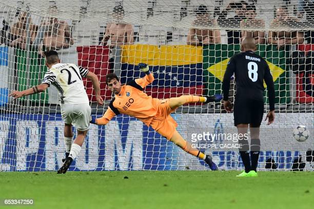 Juventus' forward from Argentina Paulo Dybala score a penalty against Porto's Spanish goalkeeper Iker Casillas during the UEFA Champions League...