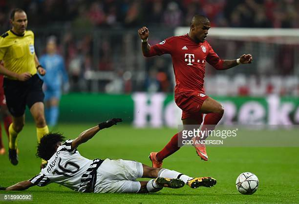 Juventus' forward from Colombia Juan Cuadrado and Bayern Munich's Brazilian midfielder Douglas Costa vie for the ball during the UEFA Champions...