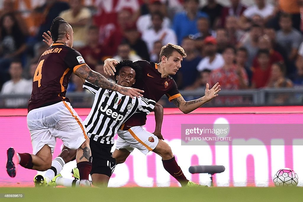 Juventus' forward from Coombia Juan Cuadrado fights for the ball with Roma's midfielder from Belgium Radja Nainggolan and Roma's defender from France...