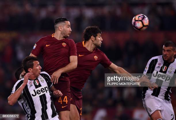 Juventus' forward from Croatia Mario Mandzukic and Juventus' midfielder from Italy Stefano Sturaro fight for the ball with Roma's defender from...