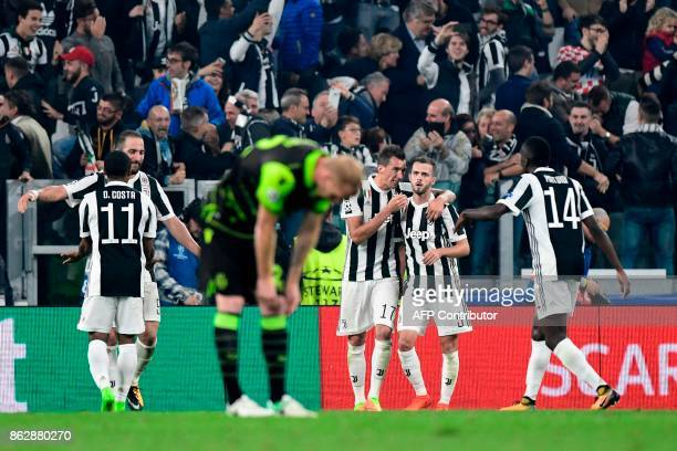 Juventus' forward from Croatia Mario Mandzukic celebrates with teammates Juventus midfielder Miralem Pjanic Juventus' midfielder from France Blaise...
