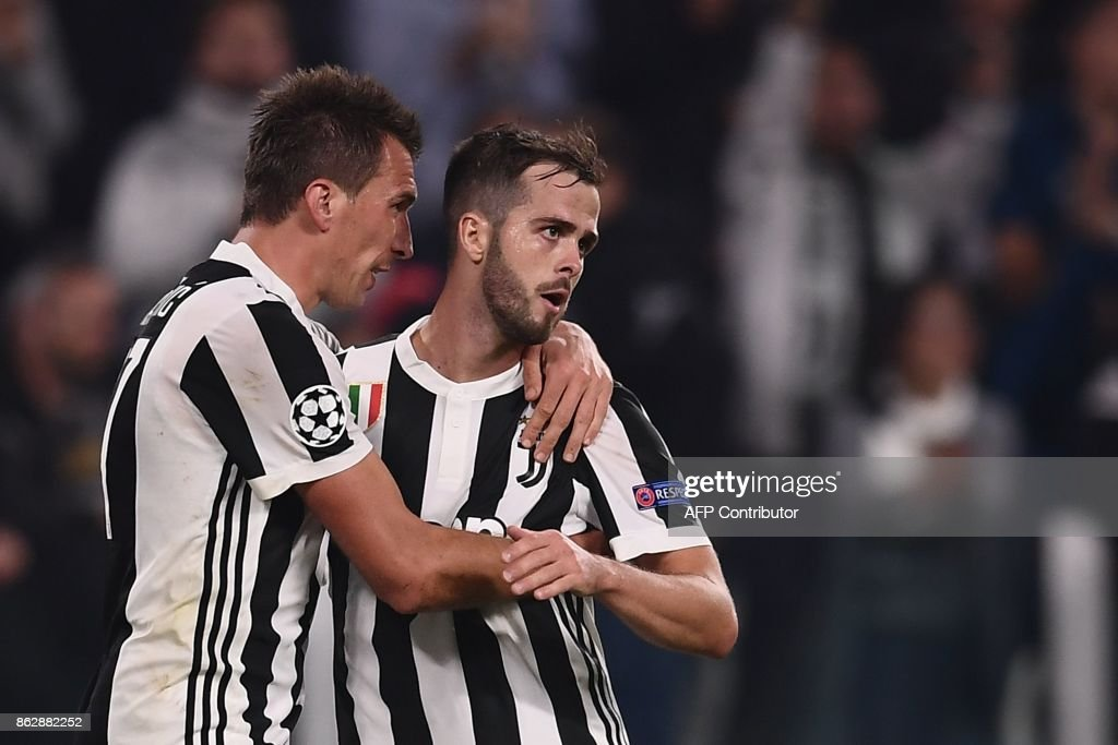 Juventus' forward from Croatia Mario Mandzukic (L) celebrates with Juventus midfielder Miralem Pjanic after scoring during the UEFA Champions League Group D football match Juventus vs Sporting CP at the Juventus stadium on October 17, 2017 in Turin. Juventus won 2-1. / AFP PHOTO / Marco BERTORELLO