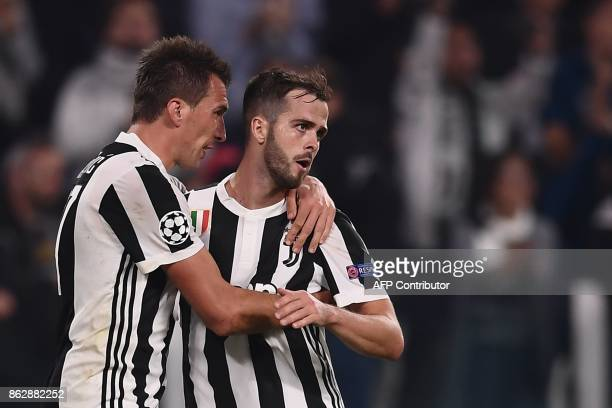 Juventus' forward from Croatia Mario Mandzukic celebrates with Juventus midfielder Miralem Pjanic after scoring during the UEFA Champions League...