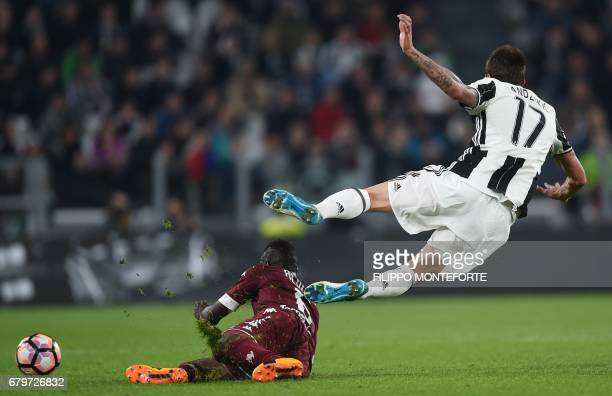 Juventus' forward from Croatia Mario Mandzukic is tackled by Torino's midfielder from Ghana Afriyie Acquah during the Italian Serie A football match...
