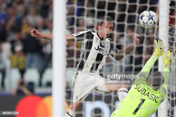 TOPSHOT Juventus' forward from Croatia Mario Mandzukic scores a goal past Monaco's Croatian goalkeeper Danijel Subasic during the UEFA Champions...