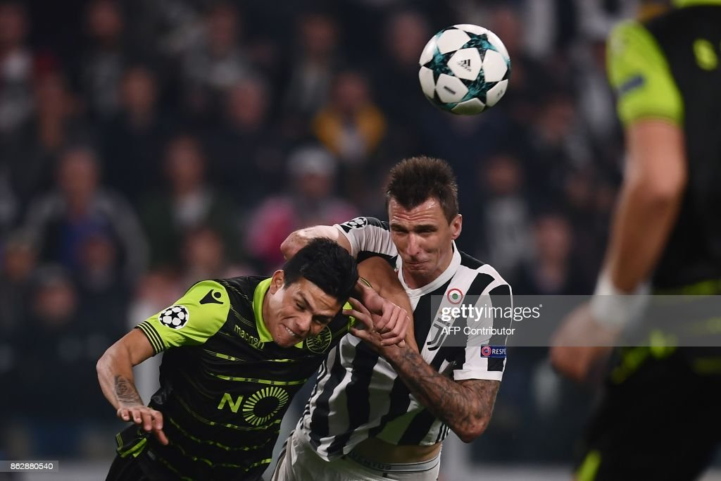 Juventus' forward from Croatia Mario Mandzukic (C) scores despite Sporting's Argentinian defender Jonathan Silva during the UEFA Champions League Group D football match Juventus vs Sporting CP at the Juventus stadium on October 17, 2017 in Turin. / AFP PHOTO / Marco BERTORELLO