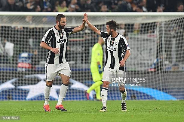 TOPSHOT Juventus' forward Gonzalo Higuain celebrates with Juventus midfielder Miralem Pjanic after scoring a penalty during the UEFA Champions League...