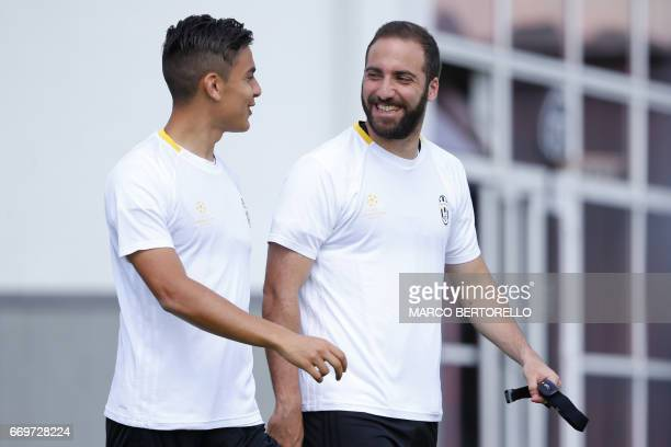 Juventus' forward Gonzalo Higuain from Argentina and Juventus' forward Paulo Dybala from Argentina chat during a training session on the eve of the...