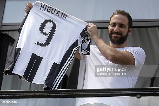 Juventus' forward Gonzalo Higuain from Argentina holds his jersey at the Juventus' headquarter in Turin on July 27 2016 Gonzalo Higuain completed a...