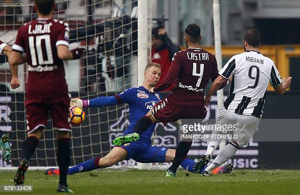 Juventus' forward Gonzalo Higuain from Argentina scores past Torino's English goalkeepter Joe Hart during the Italian Serie A football match between...