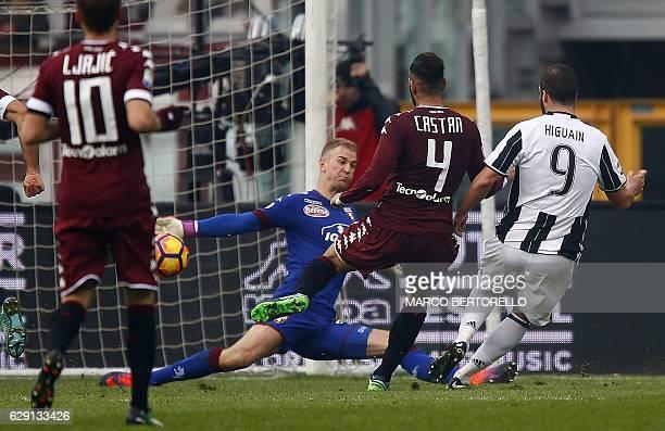 Juventus' forward Gonzalo Higuain from Argentina scores past Torino's English goalkeepter Joe Hart during the Italian Serie A football match between...