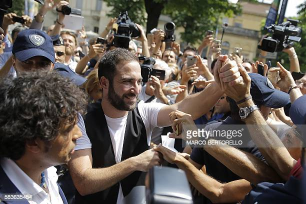 TOPSHOT Juventus' forward Gonzalo Higuain from Argentina shakes hands with supporters near the Juventus' headquarter in Turin on July 27 2016 In the...
