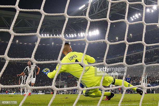 Juventus' forward Gonzalo Higuain scores a penalty kick against Lyon's Portuguese goalkeeper Anthony Lopes during the UEFA Champions League football...