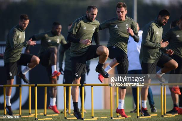 Juventus' forward Mario Mandzukic from Croatia and Juventus' defender Giorgio Chiellini attend a training session on the eve of the UEFA Champions...
