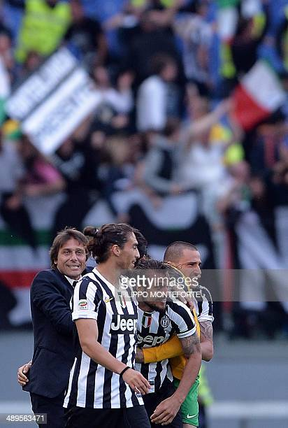 Juventus' forward Pablo Osvaldo celebrates with coach Antonio Conte and teammates after scoring at the end of the Italian Serie A football match AS...