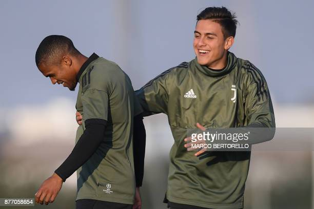 Juventus' forward Paulo Dybala from Argentina and Juventus' midfielder Douglas Costa from Brazil attend a training session on the eve of the UEFA...