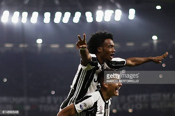 Juventus' forward Paulo Dybala from Argentina celebrates with Juventus' midfielder Juan Cuadrado from Colombia after scoring during the Italian Serie...