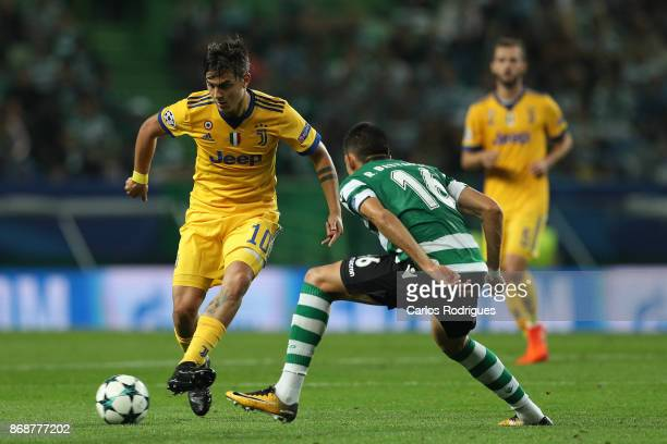 Juventus forward Paulo Dybala from Argentina tries to escape Sporting CP midfielder Rodrigo Battaglia from Argentina during the UEFA Champions League...